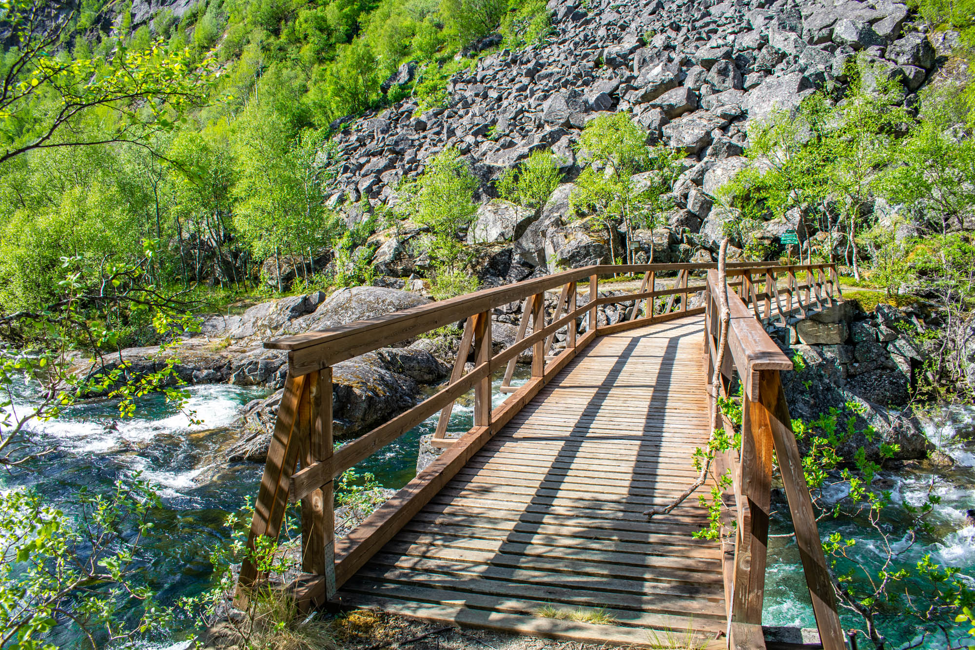 En liten bro langs Rallarveien der stien krysser Rombakselva